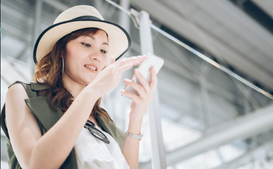 Young Woman with a Hat looking on her Smartphone